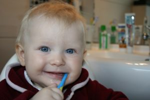 baby is brushing his teeth-important for pediatric health care