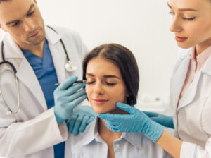 cosmetic surgeons examining a patient